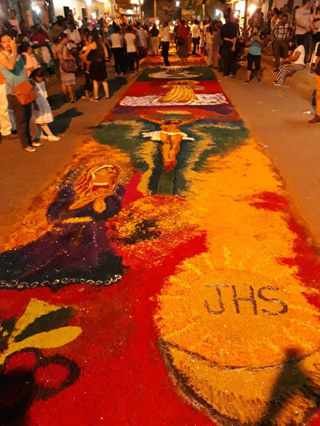 People enjoying the carpets as the procession approaches